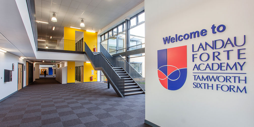 Reception area of the academy with welcome text and logo
