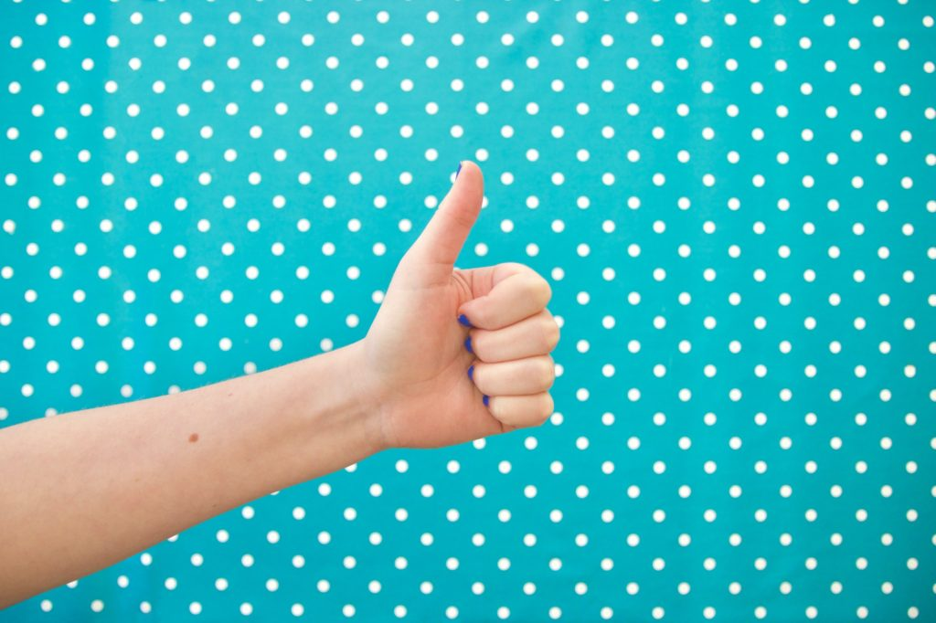 Thumbs up on bright polkadot background